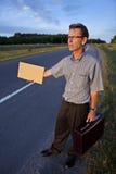 Hombre de negocios que hace autostop para trabajar fotos de archivo libres de regalías