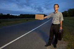 Hombre de negocios que hace autostop para trabajar Imagen de archivo