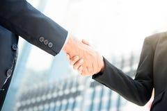 Hombre de negocios que hace el apretón de manos con una empresaria Fotografía de archivo