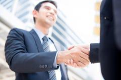 Hombre de negocios que hace el apretón de manos con una empresaria Imagen de archivo
