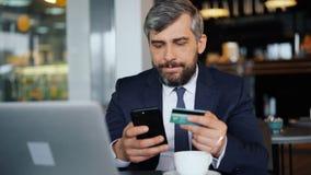Hombre de negocios que hace el pago en línea que sostiene la tarjeta y el smartphone de crédito en café almacen de metraje de vídeo