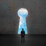 Hombre de negocios que hace frente a la puerta dominante de la forma con el cielo azul afuera Imagenes de archivo