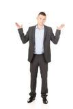 Hombre de negocios que hace gesto indeciso Imagen de archivo libre de regalías