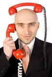 Hombre de negocios que hace juegos malabares dos llamadas Foto de archivo libre de regalías