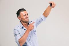Hombre de negocios que hace la foto del selfie en smartphone imágenes de archivo libres de regalías