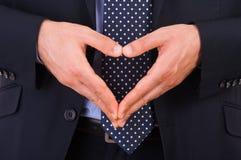 Hombre de negocios que hace símbolo del corazón con las manos. Fotografía de archivo