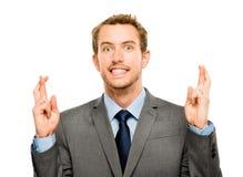 Hombre de negocios que hace un deseo aislado en el fondo blanco Imagen de archivo libre de regalías