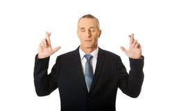 Hombre de negocios que hace un deseo con los fingeres cruzados Imágenes de archivo libres de regalías