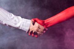 Hombre de negocios que hace un trato con el diablo Foto de archivo libre de regalías