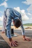 Hombre de negocios que hace yoga en un puente de madera con un ordenador portátil foto de archivo libre de regalías