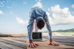 Hombre de negocios que hace yoga en un puente de madera con un ordenador portátil imagen de archivo libre de regalías