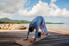 Hombre de negocios que hace yoga en un puente de madera con un ordenador portátil imagen de archivo