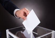 Hombre de negocios que inserta la votación en caja en el escritorio Fotos de archivo