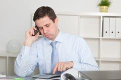 Hombre de negocios que invita al teléfono mientras que calcula Imagen de archivo libre de regalías