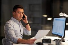 Hombre de negocios que invita a sartphone en la oficina de la noche fotografía de archivo libre de regalías