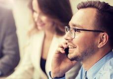 Hombre de negocios que invita a smartphone en la oficina imagenes de archivo
