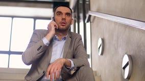 Hombre de negocios que invita a smartphone en las escaleras de la oficina almacen de metraje de vídeo
