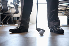 Hombre de negocios que juega al golf en su oficina, cierre para arriba en pies Imagen de archivo