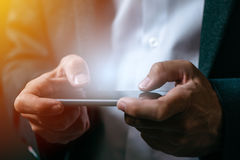 Hombre de negocios que juega al videojuego móvil del app en el teléfono elegante Fotografía de archivo