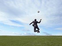 Hombre de negocios que juega a fútbol Foto de archivo