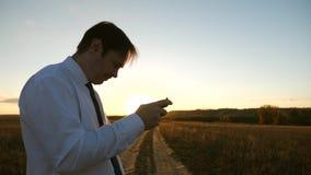 Hombre de negocios que juega a juegos de la tableta en el parque en los rayos calientes de la puesta del sol hombre que juega a j almacen de video