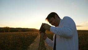 Hombre de negocios que juega a juegos de la tableta en el parque en los rayos calientes de la puesta del sol hombre que juega a j almacen de metraje de vídeo