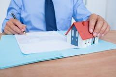 Hombre de negocios que lee un contrat antes de firmarlo Foto de archivo libre de regalías