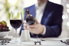 Hombre de negocios que lee una etiqueta de la botella de vino en restaurante foto de archivo libre de regalías