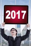 Hombre de negocios que levanta encima de los números 2017 en un tablero Fotos de archivo