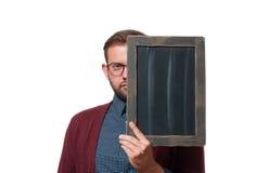 Hombre de negocios que lleva a cabo al tablero negro vacío imagen de archivo