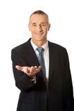 Hombre de negocios que lleva a cabo algo en su palma Fotos de archivo libres de regalías