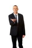 Hombre de negocios que lleva a cabo algo en su palma Fotos de archivo