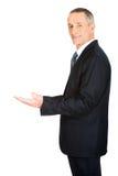 Hombre de negocios que lleva a cabo algo invisible Fotografía de archivo libre de regalías