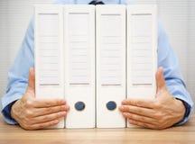 Hombre de negocios que lleva a cabo carpetas concepto el considerar, de las finanzas o de la ley Fotografía de archivo libre de regalías