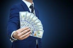 Hombre de negocios que lleva a cabo dólares del efectivo del dinero en manos de pasarlas al cliente Hombre de negocios que da el  fotografía de archivo