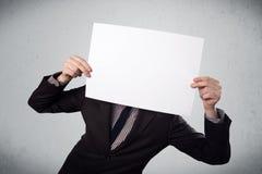 Hombre de negocios que lleva a cabo delante el suyo la cabeza un papel con el espacio de la copia Imágenes de archivo libres de regalías