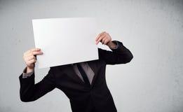 Hombre de negocios que lleva a cabo delante el suyo la cabeza un papel con el espacio de la copia imagen de archivo