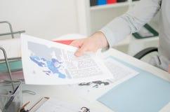 Hombre de negocios que lleva a cabo documentos económicos Foto de archivo libre de regalías