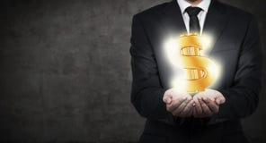 Hombre de negocios que lleva a cabo el dólar del oro Imagen de archivo libre de regalías
