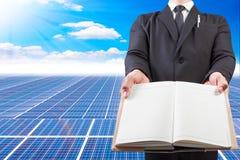 Hombre de negocios que lleva a cabo el espacio en blanco del libro para el espacio de trabajo en la energía solar po Imagen de archivo