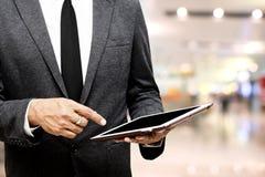 Hombre de negocios que lleva a cabo el foco selectivo de la tableta del ordenador en señalar Foto de archivo