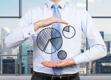 Hombre de negocios que lleva a cabo el gráfico de sectores Imágenes de archivo libres de regalías