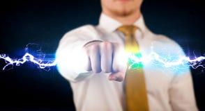 Hombre de negocios que lleva a cabo el perno ligero de la electricidad en sus manos Foto de archivo libre de regalías