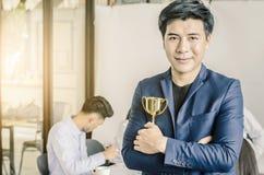 Hombre de negocios que lleva a cabo el premio del trofeo para el éxito en negocio, fotos de archivo