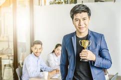Hombre de negocios que lleva a cabo el premio del trofeo para el éxito en negocio, imágenes de archivo libres de regalías