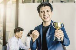 Hombre de negocios que lleva a cabo el premio del trofeo para el éxito en negocio, fotografía de archivo libre de regalías