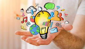 Hombre de negocios que lleva a cabo iconos dibujados mano de la bombilla y de las multimedias Foto de archivo libre de regalías