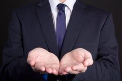 Hombre de negocios que lleva a cabo la mano que presenta el producto Foto de archivo libre de regalías