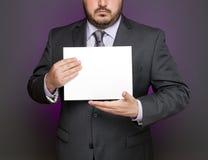 Hombre de negocios que lleva a cabo la muestra en blanco Imagen de archivo