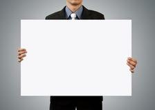 Hombre de negocios que lleva a cabo la muestra y la mano en blanco Imágenes de archivo libres de regalías